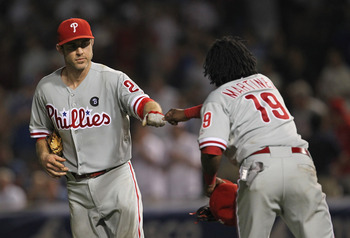 CHICAGO, IL - JULY 19:  Michael Martinez #19 of the Philadelphia Phillies is congratulated by teammate Chase Utley #26 after hitting a double, scoring two runs, in the 9th inning against the Chicago Cubs at Wrigley Field on July 19, 2011 in Chicago, Illli