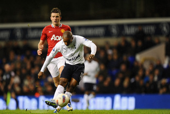 Tottenham Hotspur's Jermain Defoe shapes up to strike the ball as Manchester United's Michael Carrick looks on.