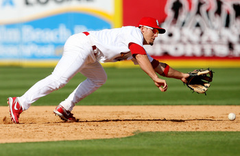 JUPITER, FL - FEBRUARY 25:  Third baseman Tyler Greene #67 of the St. Louis Cardinals fails to stop a single by Robert Andino #11 of the Florida Marlins in the eighth inning during a spring training game at Roger Dean Stadium February 25, 2009 in Jupiter,