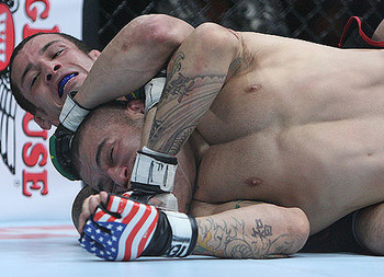 Cristiano Marcello (rear) secures a rear-naked choke (courtesy of Sherdog).