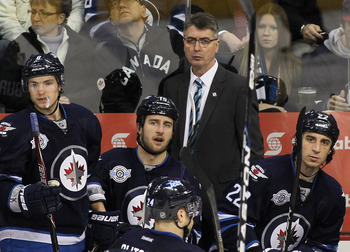 WINNIPEG, CANADA - MARCH 5: Alexander Burmistrov #8, Tanner Glass #15, head coach Claude Noel and Chris Thorburn #22 of the Winnipeg Jets watch the action in a game against the Buffalo Sabres in NHL action at the MTS Centre on March 5, 2012 in Winnipeg, M