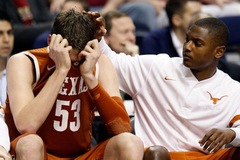 NASHVILLE, TN - MARCH 16:  Clint Chapman (L) #53 of the Texas Longhorns hides his head in his jersey on the bench against the Cincinnati Bearcats during the second round of the 2012 NCAA Men's Basketball Tournament at Bridgestone Arena on March 16, 2012 i