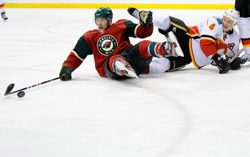 ST PAUL, MN - MARCH 11: Darroll Powe #14 of the Minnesota Wild attempts to control the puck after he and Jay Bouwmeester #4 of the Calgary Flames fell to the ice during the third period on March 11, 2012 at Xcel Energy Center in St Paul, Minnesota. The Fl