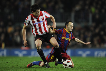 BARCELONA, SPAIN - FEBRUARY 20:  Andres Iniesta of FC Barcelona (R) fights for the ball against Javi Martinez of Athletic Bilbao during the La Liga match between FC Barcelona and Athletic Bilbao at Camp Nou on February 20, 2011 in Barcelona, Spain. Barcel