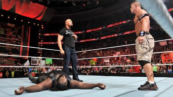 The Rock and John Cena standing over Mark Henry, photo copyright to WWE.com