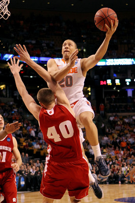 BOSTON, MA - MARCH 22:  Brandon Triche #20 of the Syracuse Orange draws contact against Jared Berggren #40 of the Wisconsin Badgers while driving to the basket during their 2012 NCAA Men's Basketball East Regional Semifinal game at TD Garden on March 22,