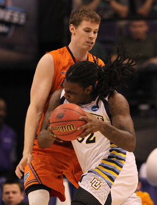 PHOENIX, AZ - MARCH 22:  Jae Crowder #32 of the Marquette Golden Eagles drives on Erik Murphy #33 of the Florida Gators in the second half during the 2012 NCAA Men's Basketball West Regional Semifinal game at US Airways Center on March 22, 2012 in Phoenix
