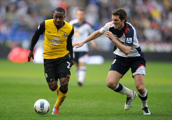 BOLTON, ENGLAND - MARCH 24: Junior Hoilett of Blackburn and Sam Ricketts of Bolton battle for the ball during the Barclays Premier League match between Bolton Wanderers and Blackburn Rovers at Reebok Stadium on March 24, 2012 in Bolton, England.  (Photo b
