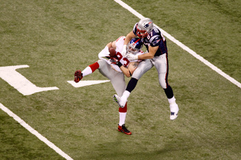INDIANAPOLIS, IN - FEBRUARY 05:  Chase Blackburn #93 of the New York Giants intercepts a pass thrown by Tom Brady #12 in the second quarter in front of Rob Gronkowski #87 of the New England Patriots during Super Bowl XLVI at Lucas Oil Stadium on February