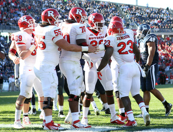 EAST HARTFORD, CT - NOVEMBER 26:  Jawan Jamison #23 of the Rutgers Scarlet Knights is congratulated by teammates Betim Bujari #55,Malcolm Bush #88 and Desmond Wynn #70 after Jamison scored a touchdown in the second quarter against the Connecticut Huskies