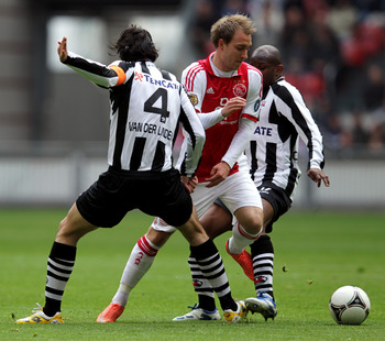 AMSTERDAM, NETHERLANDS - APRIL 01:  Christian Eriksen of Ajax gets between Antoine van der Linden (#4) and Kwame Quansah of Heracles during the Eredivisie match between Ajax Amsterdam and SC Heracles Almelo at Amsterdam Arena on April 1, 2012 in Amsterdam