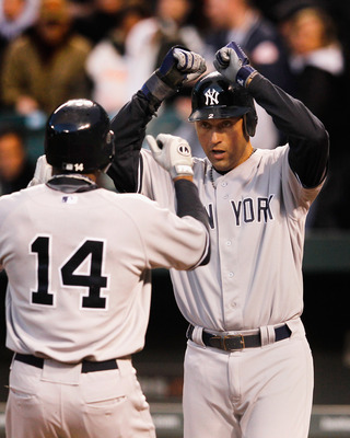 BALTIMORE, MD - APRIL 11: Curtis Granderson #14 is greeted at home plate by Derek Jeter #2 of the New York Yankees after hitting a two RBI home run during the first inning against the Baltimore Orioles at Oriole Park at Camden Yards on April 11, 2012 in B