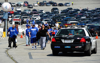 Fans walk toward Dodger Stadium before the team's home opener on Tuesday. The A's need to cut parking prices to help draw fans.