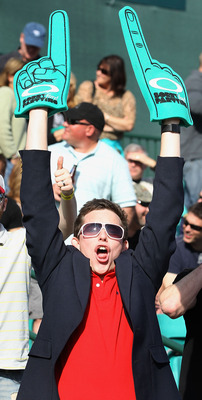 A fan hoists two foam fingers above his head during the Waste Management Phoenix Open.