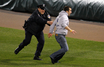 A fan tries to scurry away from a police officer during a game between the New York Yankees vs. the Baltimore Orioles.
