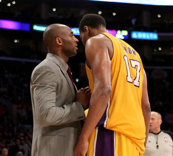 Kobe offers  teammate Andrew Bynum some advice while on the bench in a suit.