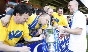AFC Wimbledon's captain, Jason Goodliffe, celebrates Conference Championship Trophy with faithful fans