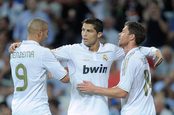 MADRID, SPAIN - SEPTEMBER 24:  Cristiano Ronaldo (C) of Real Madrid celebrates with Karim Benzema (L) and Xabi Alonso after he scored Real's 4th goal during the La Liga match between Real Madrid and Rayo Vallecano at Estadio Santiago Bernabeu on September