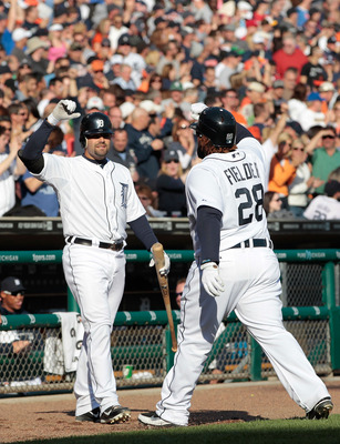 Fielder high-fives Avila after scoring a run.