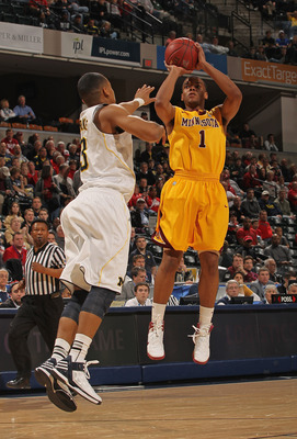 INDIANAPOLIS, IN - MARCH 09: Andre Hollins #1 of the Minnesota Golden Gophers puts up a shot over Trey Burke #3 of the Michigan Wolverines during the Big Ten Basketball Tournament Quarterfinals at Bankers Life Fieldhouse on March 9, 2012 in Indianapolis,