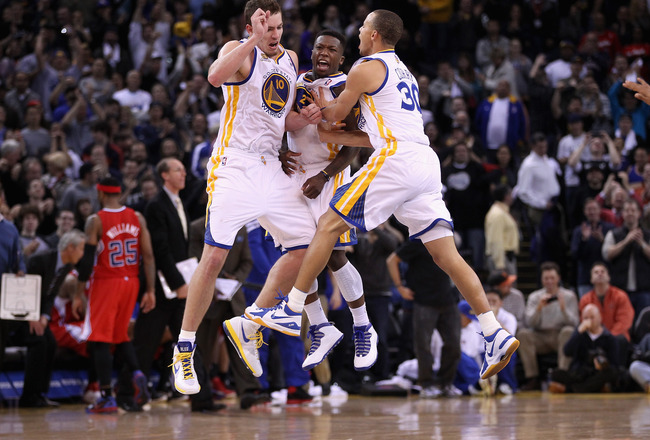 OAKLAND, CA - FEBRUARY 20:  David Lee #10 (L), Nate Robinson #2, and Stephen Curry #30 of the Golden State Warriors celebrate after Robinson made a basket in the fourth quarter of their game against the Los Angeles Clippers at Oracle Arena on February 20,