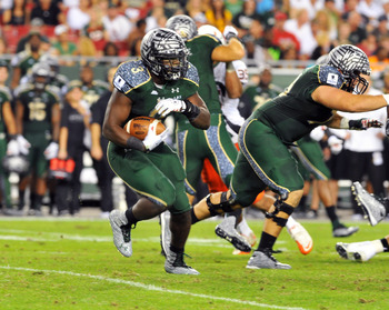 TAMPA, FL - NOVEMBER 19:  Running back Darrell Scott #3 of the  South Florida Bulls rushes upfield against the Miami Hurricanes November 19, 2011 at Raymond James Stadium in Tampa, Florida.  Miami won 6 - 3. (Photo by Al Messerschmidt/Getty Images)