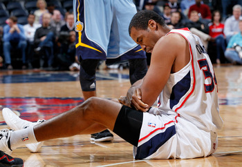 ATLANTA, GA - FEBRUARY 02:  Jason Collins #34 of the Atlanta Hawks holds onto his arm after injuring it against the Memphis Grizzlies at Philips Arena on February 2, 2012 in Atlanta, Georgia.  NOTE TO USER: User expressly acknowledges and agrees that, by