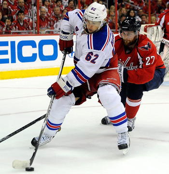Rangers forward Carl Hagelin protects the puck from Capitals defenseman Karl Alzner.