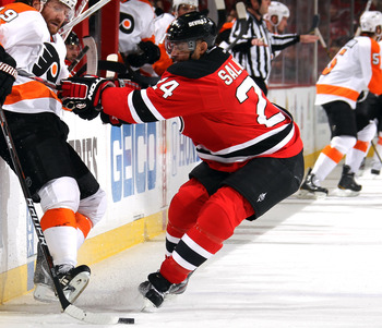 Devils defenseman Bryce Salvador battles the Flyers' Scott Hartnell for a loose puck.