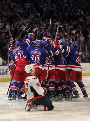 NEW YORK, NY - MAY 07:  Marc Staal #18 of the New York Rangers celebrates with his teammates after scoring the winning goal in overtime against Braden Holtby #70 of the Washington Capitals as Matt Hendricks #26 of the Washington Capitals slides to the ice