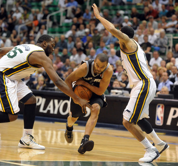 SALT LAKE CITY, UT - MAY 7:  Tony Parker #9 of the San Antonio Spurs drives to the basket on Al Jefferson #25 and and Devin Harris #5 of the Utah Jazz during the first quarter of Game Four of the Western Conference Quarterfinals in the 2012 NBA Playoffs a