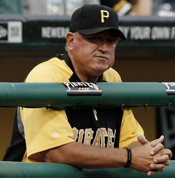 Pirates' manager Clint Hurdle attentively observes his players from the dugout.
