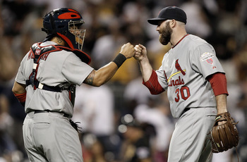 Cardinals' catcher Yadier Molina (left) and closer Jason Motte (right) celebrate a victory against the Pirates.