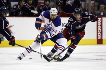 COLUMBUS, OH - JANUARY 17:  Ryan Smyth #94 of the Edmonton Oilers skates the puck up ice against Samuel Pahlsson #26 of the Columbus Blue Jackets during their game at Nationwide Arena on January 17, 2012 in Columbus, Ohio.  (Photo by John Grieshop/Getty I