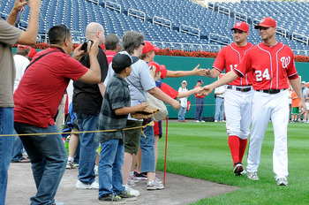 WASHINGTON, DC - SEPTEMBER 03:  Ryan Zimmerman #11 and Rick Ankiel #24 of the Washington Nationals meet with fans before the game against the New York Mets at Nationals Park on September 3, 2011 in Washington, DC.  (Photo by Greg Fiume/Getty Images)