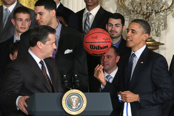 WASHINGTON, DC - MAY 04: Wildcat Coach John Calipari watches as U.S. President Barack Obama plays with a ball given to him by the University of Kentucky basketball team during an event in the East Room at the White House, on May 4, 2012 in Washington, DC.