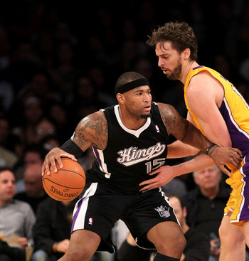 DeMarcus Cousins tries to dribble by Pau Gasol.