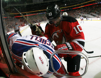 NEWARK, NJ - MAY 21:  Peter Harrold #10 of the New Jersey Devils and John Mitchell #34 of the New York Rangers vie for the puck in Game Four of the Eastern Conference Final during the 2012 NHL Stanley Cup Playoffs at the Prudential Center on May 21, 2012
