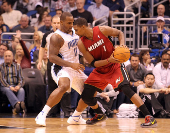 ORLANDO, FL - FEBRUARY 08: Chris Bosh #1 of the Miami Heat is guarded by Glen Davis #11 of the Orlando Magic during the game at Amway Center on February 8, 2012 in Orlando, Florida.   NOTE TO USER: User expressly acknowledges and agrees that, by downloadi