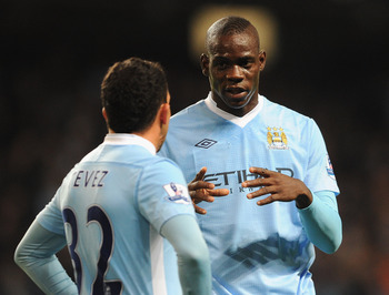 MANCHESTER, ENGLAND - SEPTEMBER 21:  Mario Balotelli of Manchester City speaks to team mate Carlos Tevez during the Carling Cup Third Round match between Manchester City and Birmingham City at the Etihad Stadium on September 21, 2011 in Manchester, Englan
