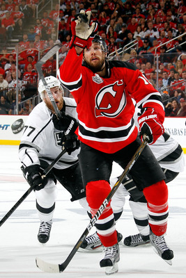 NEWARK, NJ - JUNE 09: Travis Zajac #19 of the New Jersey Devils reaches for a loose puck as Jeff Carter #77 of the Los Angeles Kings looks on during Game Five of the 2012 NHL Stanley Cup Final at the Prudential Center on June 9, 2012 in Newark, New Jersey
