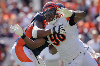 DENVER, CO - SEPTEMBER 18:  Defensive end Carlos Dunlap #96 of the Cincinnati Bengals rushes as offensive tackle Orlando Franklin #74 of the Denver Broncos blocks to protect quarterback Kyle Orton #8 of the Denver Broncos at Sports Authority Field at Mile