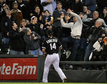 CHICAGO, IL - APRIL 17:   A fan uses his cup as a glove to catch a foul ball as first baseman Paul Konerko #14 of the Chicago White Sox watches during the fifth inning against the Baltimore Orioles at U.S. Cellular Field on April 17, 2012 in Chicago, Illi