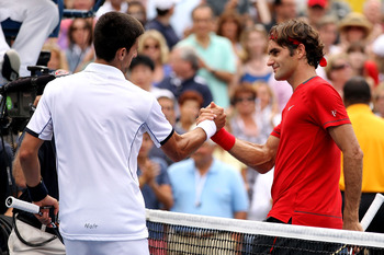 Smiling thru the pain: Federer and Djokovic shake hands after the Serbs incredible comeback at the 2011 US Open