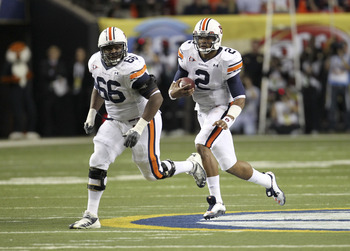 ATLANTA - DECEMBER 4:  Quarterback Cam Newton #2 of the Auburn Tigers (right) runs with the ball while offensive lineman Mike Berry runs with him during the 2010 SEC Championship against the South Carolina Gamecocks at Georgia Dome on December 4, 2010 in