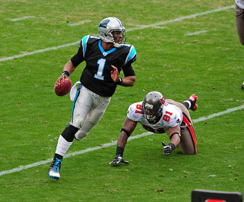 Cam Newton shakes off a tackler in Carolina's 48-16 win over Tampa Bay on Christmas Eve 2011.