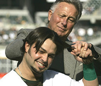 Steve Swisher cuts his son's hair on the field in 2007, courtesy of charlespaolino.wordpress.com.