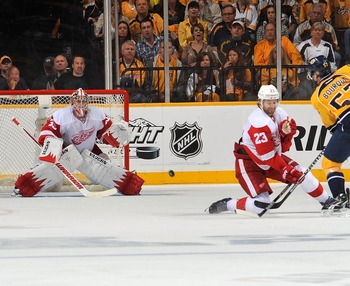 NASHVILLE, TN - APRIL 20:  Gabriel Bourque #57 of the Nashville Predators takes a shot past Brad Stuart #23 of the Detroit Red Wings on goalie Jimmy Howard #35 in Game Five of the Western Conference Quarterfinals during the 2012 NHL Stanley Cup Playoffs a