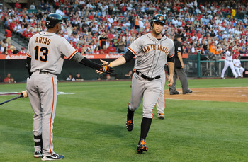 Brandon Belt is greeted by Joaquin Arias after scoring a run.