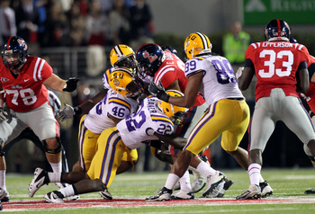 OXFORD, MS - NOVEMBER 19: Ryan Baker #22, Kevin Minter #46 and Lavar Edwards #89 of the LSU Tigers tackle Enrique Davis #27 of the Ole Miss Rebels on November 19, 2011 at Vaught-Hemingway Stadium in Oxford, Mississippi. LSU beat Mississippi 52-3. (Photo b